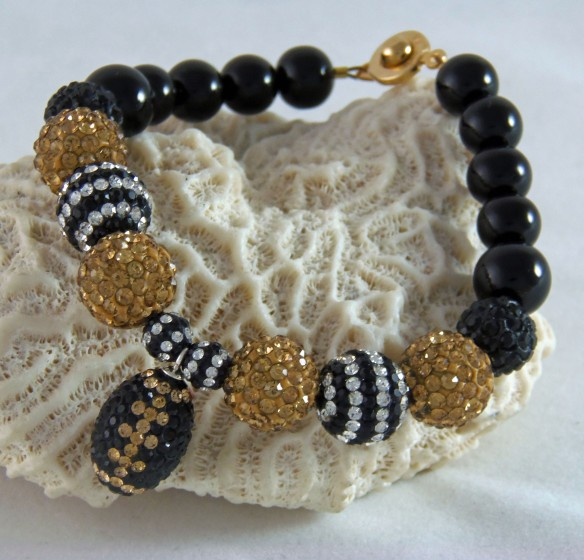 This shimmering New Orleans Saints-inspired design also features a cute pave crystal football charm. I can design bracelets for any team.